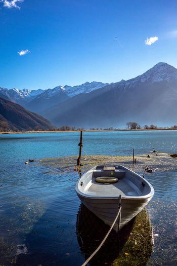 Sailboats Moored On Lake By Mountains Against Blue Sky