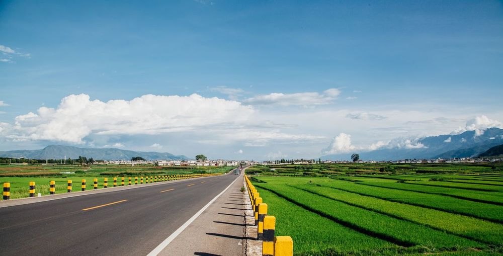 Country Road Amidst Fields Against Cloudy Sky