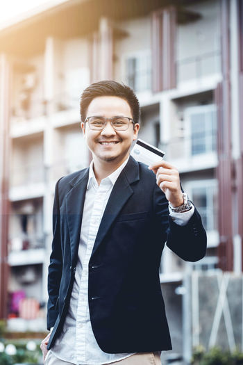 Portrait of smiling businessman holding credit card against building