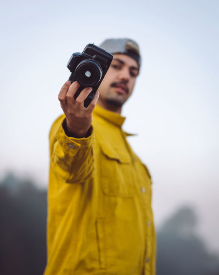 Young man photographing against sky