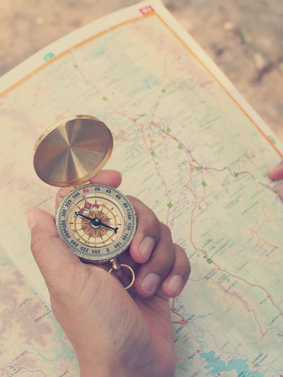 Advanture Close-up Compass Direction Exploration Finger Guidance Hand Holding Human Body Part Human Hand Indoors  Journey Map Navigational Compass Navigational Equipment Real People Searching Tour Travel Destinations