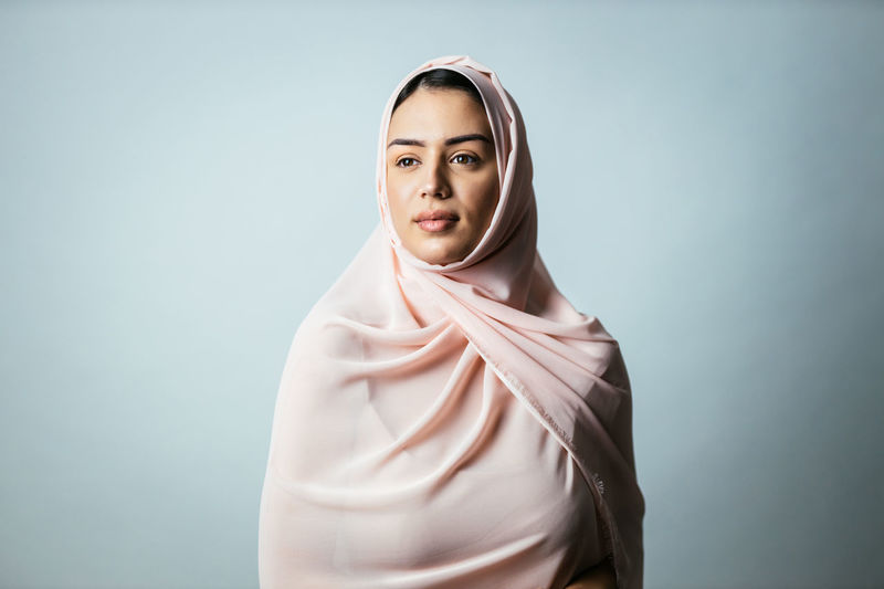 Young woman wearing hijab standing against gray background
