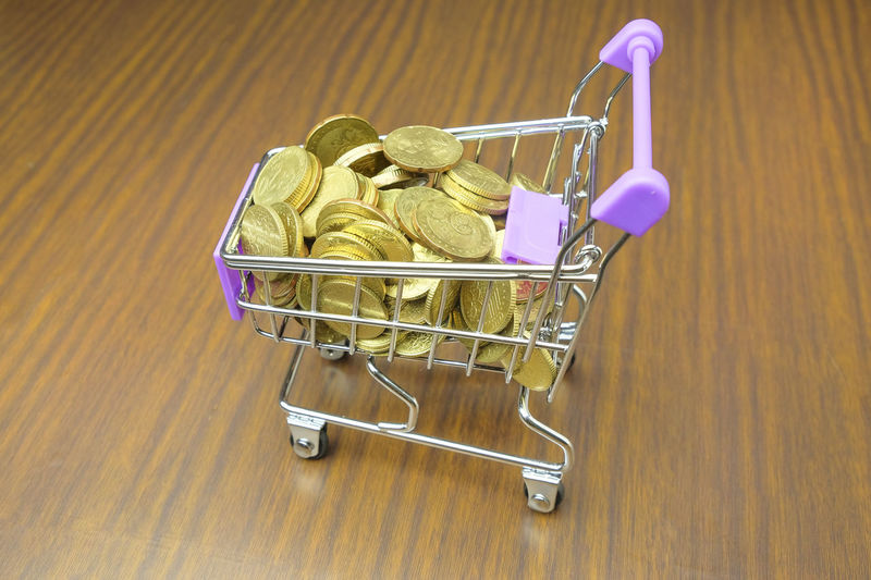 High angle view of coins in shopping cart on wooden table