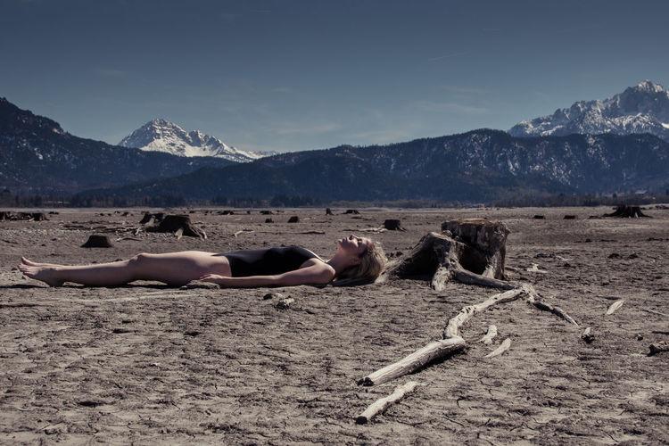 Woman lying on mountain against sky