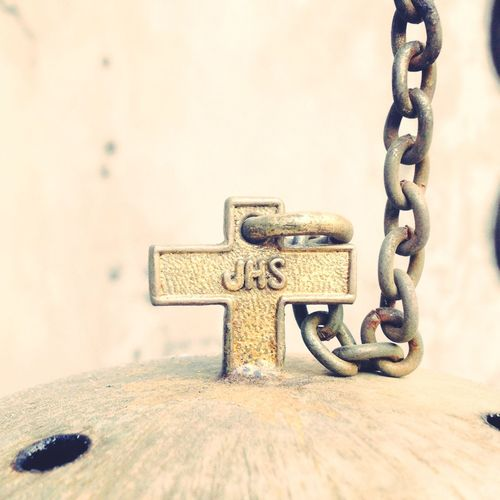 Close-up of chain on metal cross