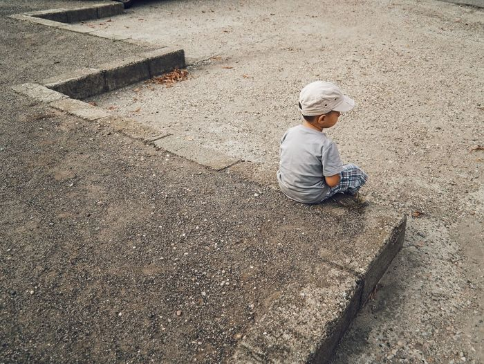 High angle view of boy looking away sitting on footpath