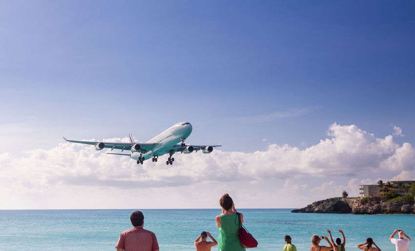 People at airplane flying over sea against sky