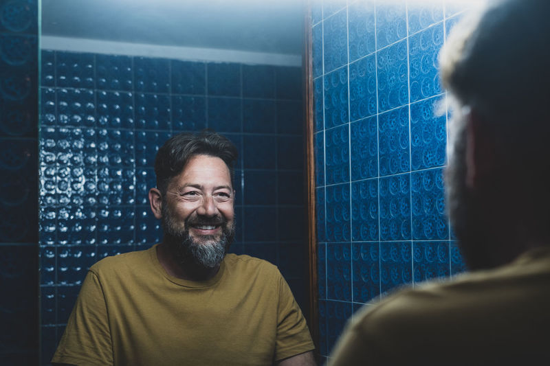 Smiling man looking at mirror in bathroom