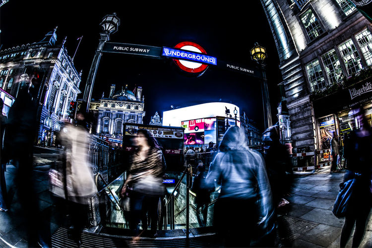 """""""Underground"""" Blurred Motion Casual Clothing City City Life Crowd Dark Group Of People Holding Illuminated International Landmark Lifestyles Men Night Outdoors Person Piccadilly Circus Rear View Rush Hour"""