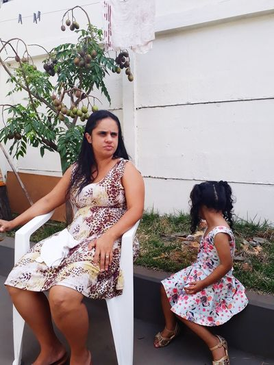 Mother and daughter sitting in yard