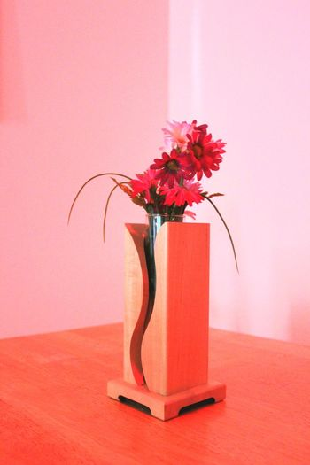 Close-up of red flower vase on table against wall