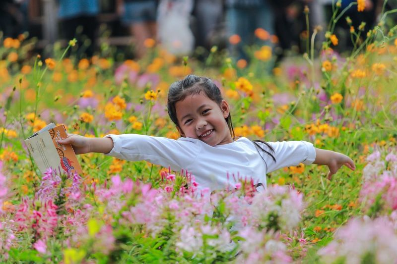 Portrait of happy girl standing amidst flowers