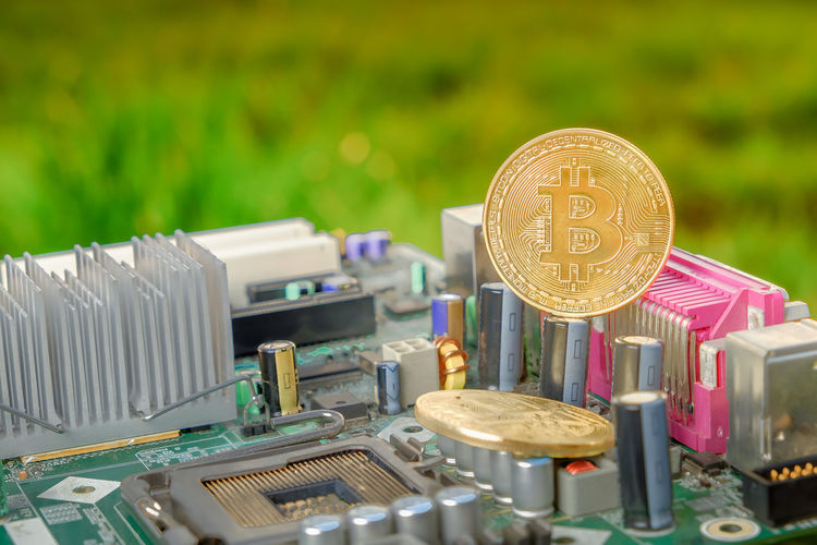 Bitcoin with a motherboard, Golden Bitcoin Cryptocurrency on computer circuit board with blurred green nature while sunrise. The concept of cryptocurrency. Blockchain technology. Business Close-up Coin Communication Currency Day Economy Equipment Finance Focus On Foreground Food And Drink Gold Colored Large Group Of Objects Machinery Metal No People Number Outdoors Still Life Technology Text