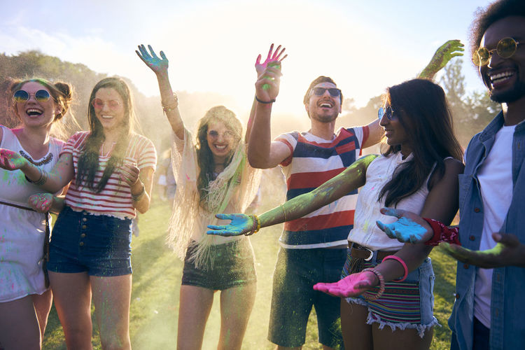 Happy friends enjoying carnival with paint powder