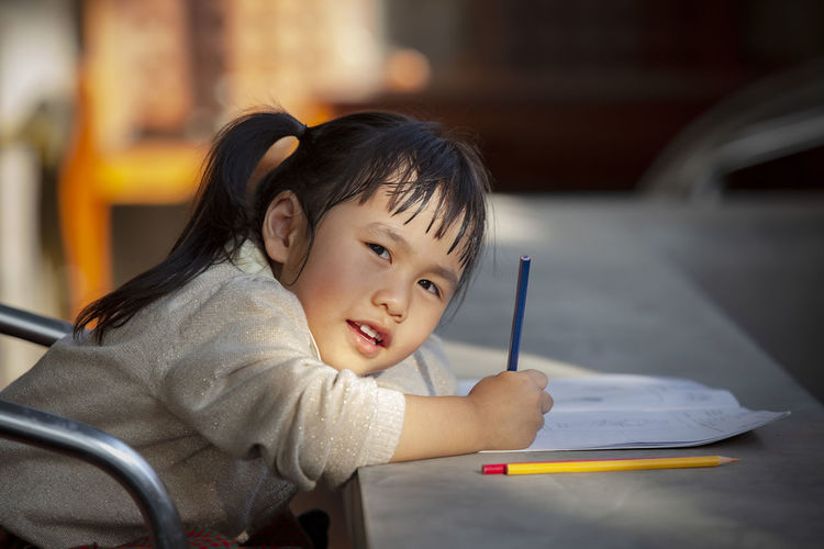Portrait of girl drawing in book on table