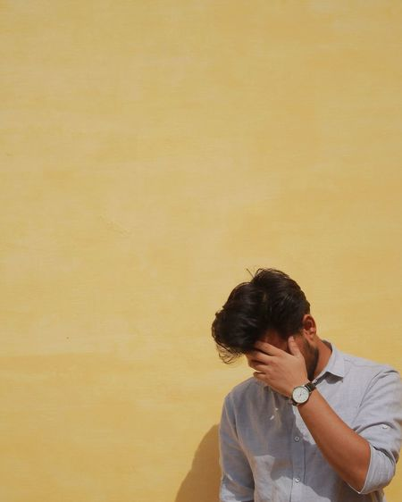 Young Man Obscuring Face Against Yellow Wall