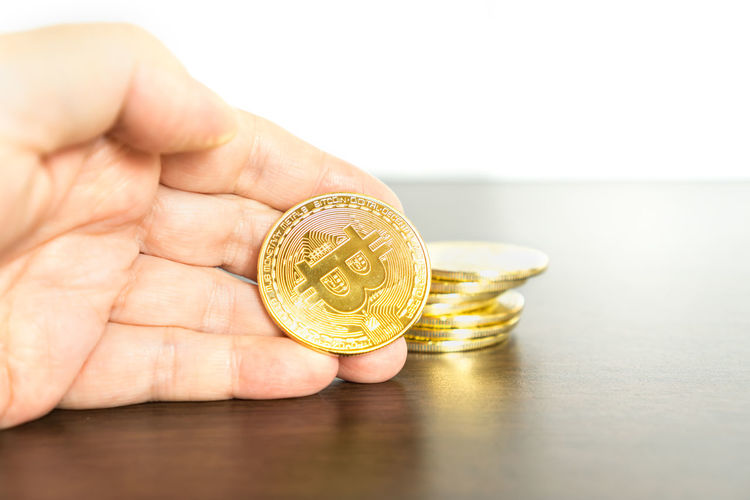 Adult Bitcoin Bitcoin Miner Bitcoin Mining Bitcoins Business Close-up Coin Currency Day Finance Financial Gold Gold Colored Holding Human Body Part Human Hand Indoors  One Person People Savings Stack Table Wealth White Background