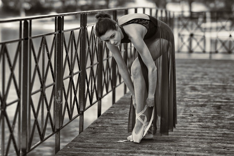 Full Length Of Ballet Dancer Wearing Shoes While Standing On Bridge