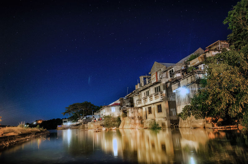 Reflection Of Illuminated Buildings On Calm River At Night