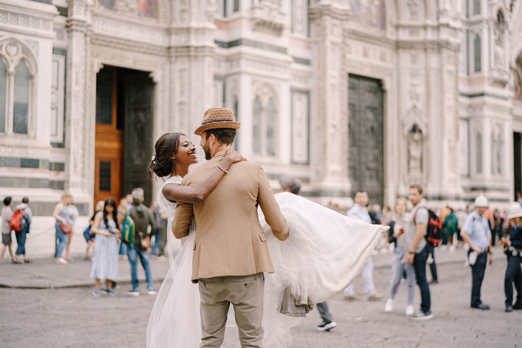 Couple embracing in front of building on street