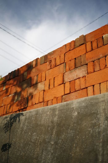 Sky Architecture Built Structure Wall Building Exterior Low Angle View No People Wall - Building Feature Day Brick Wall Brick Cloud - Sky Outdoors Surrounding Wall In A Row Sunlight Concrete Building Stone Wall Pattern Shadow Floral Pattern