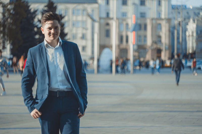 Young businessman standing in city