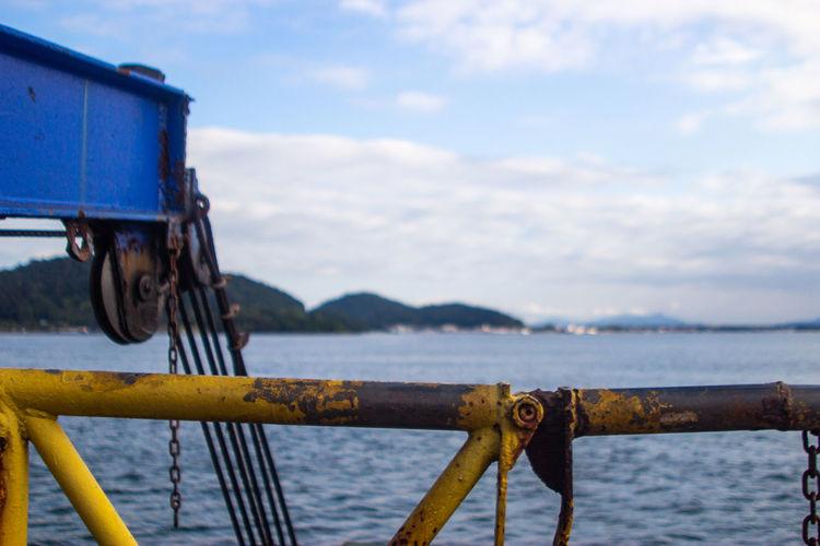 Rusty metal by sea against sky