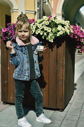 Full length of girl standing by flowering plants