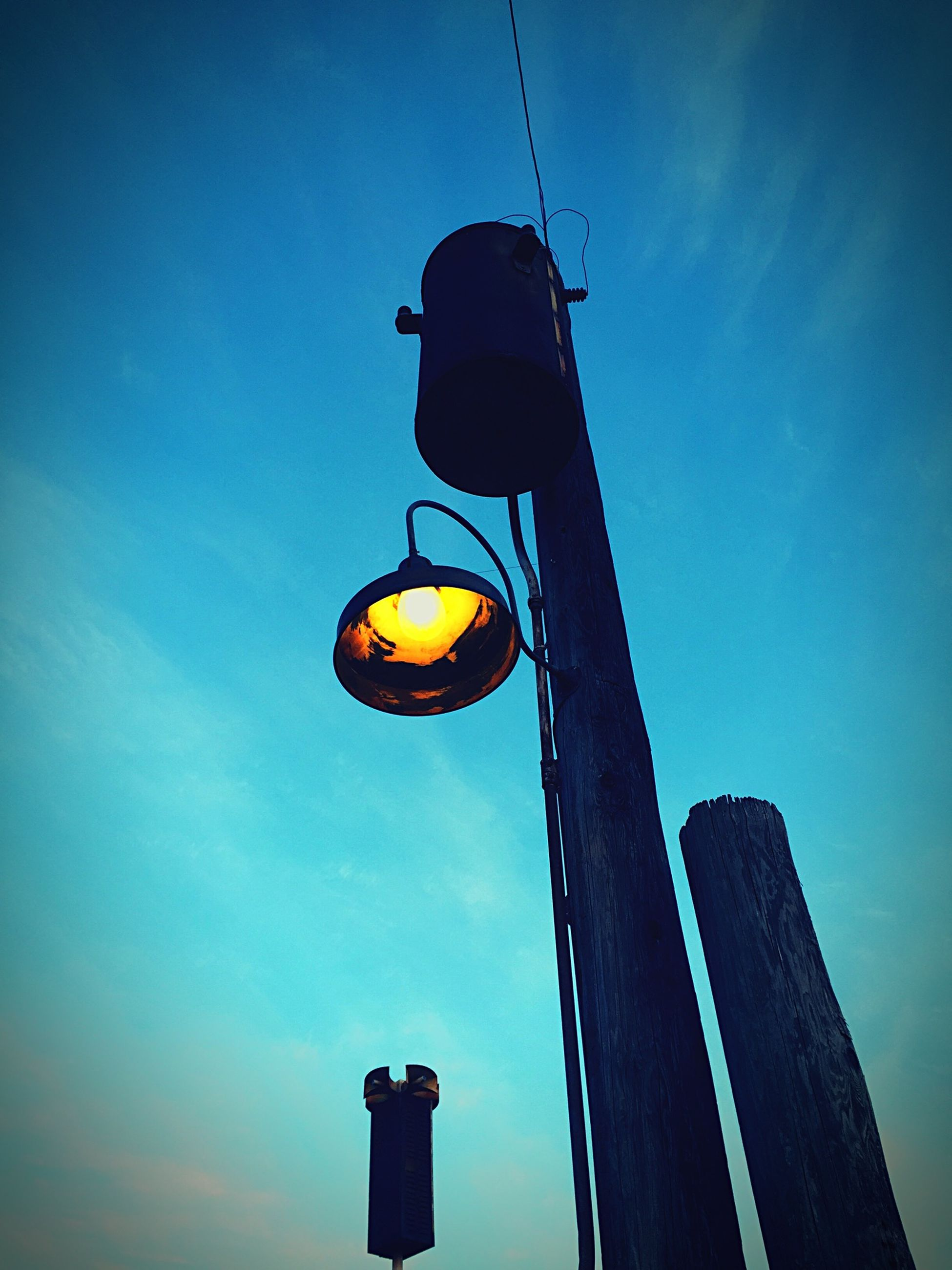 low angle view, lighting equipment, clear sky, sky, street light, blue, built structure, architecture, sunset, electricity, copy space, electric light, building exterior, illuminated, no people, outdoors, dusk, lantern, hanging, pole