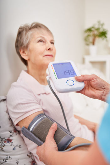 Cropped image of doctor checking blood pressure of senior woman