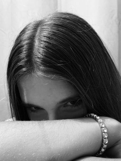 Close-up portrait of young woman hiding face