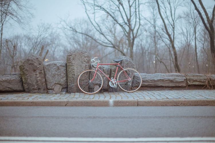 Bicycle leaning against rock fence