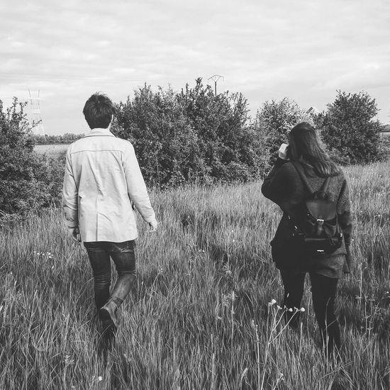 Rear view of friends walking on field against sky