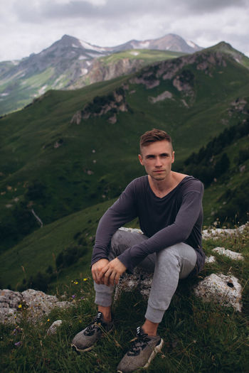 Portrait of young man sitting on mountain