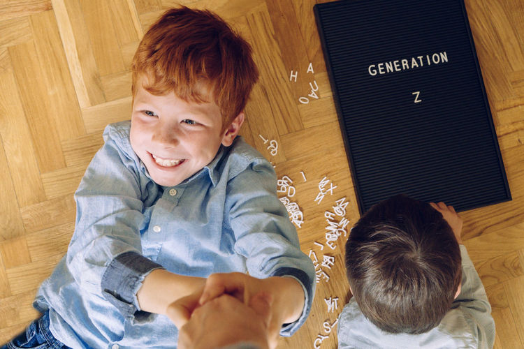 High angle view of smiling boy by sibling playing with alphabets