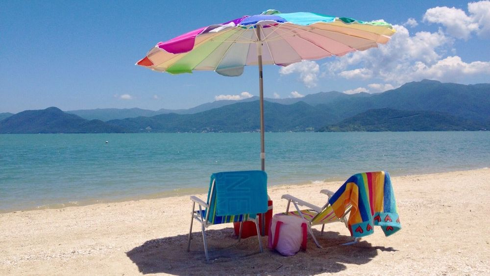 Mountain Water Umbrella Tranquil Scene Mountain Range Tranquility Beach Scenics Multi Colored Yellow Sea Clear Sky Nature Shore Blue Vacations Day Tourism Beauty In Nature Outdoors
