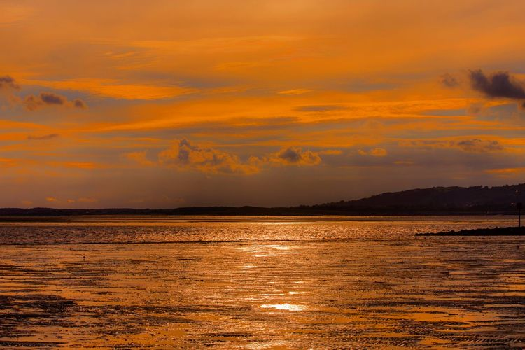 Sunset Scenics Orange Color Tranquil Scene Water Beauty In Nature Tranquility Sea Waterfront Idyllic Nature Cloud - Sky Dramatic Sky Rippled Sky Cloud Vibrant Color Majestic Romantic Sky Atmospheric Mood