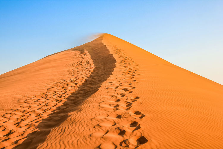 Low angle view of sand dunes in desert against clear sky