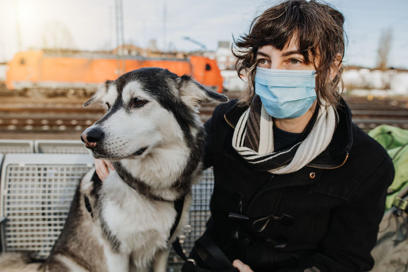 Woman wearing mask sitting with dog outdoors