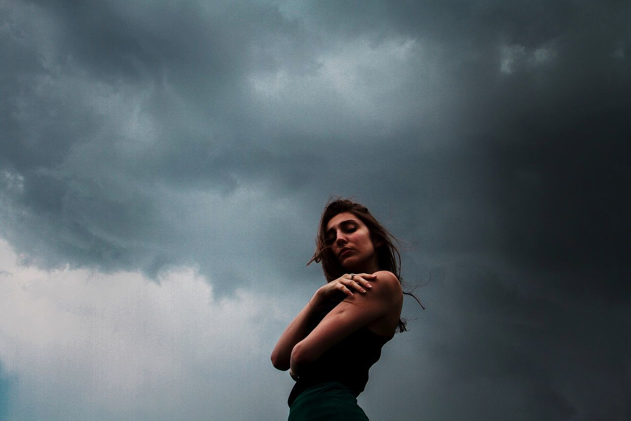 Young woman against stormy sky
