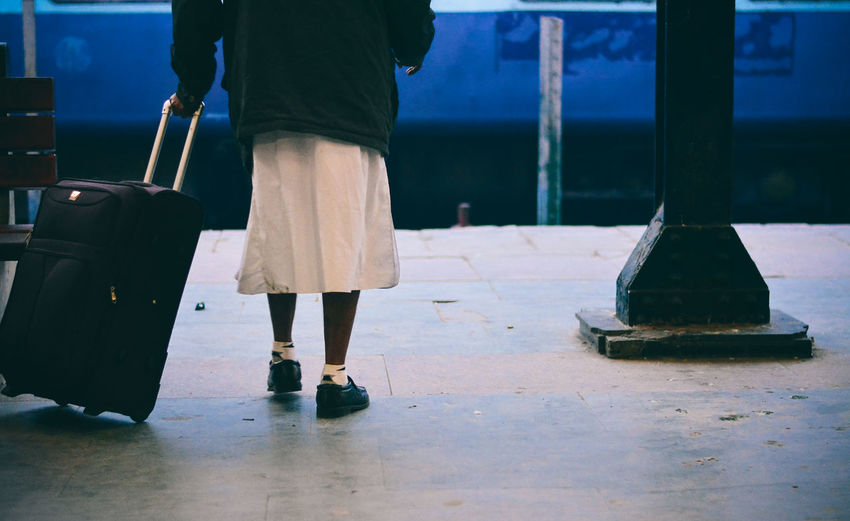 Low section of woman with luggage at railroad station platform