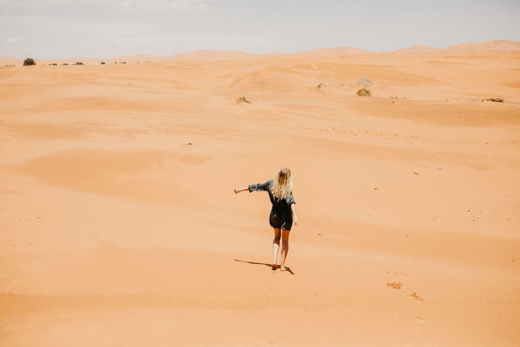 Woman Walking On Desert In Sunny Day