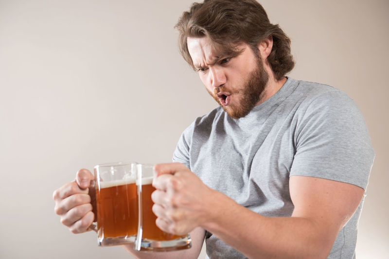 Mid adult man holding beer glass against white background