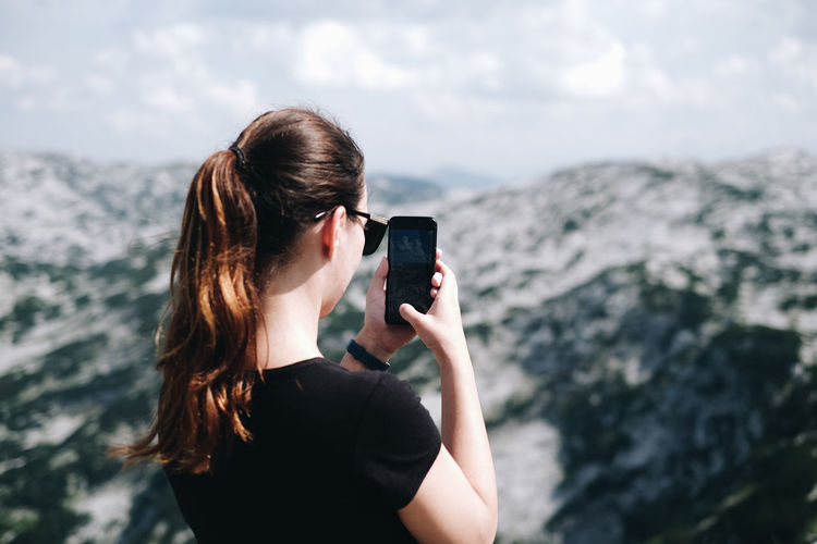 Rear view of woman photographing through mobile phone