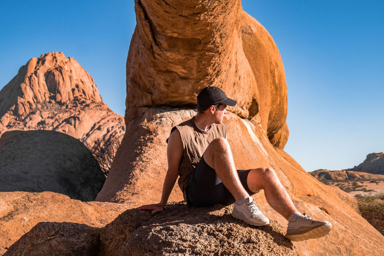 Man looking away while sitting on rock formation