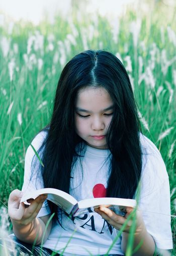 Girl reading book on lawn