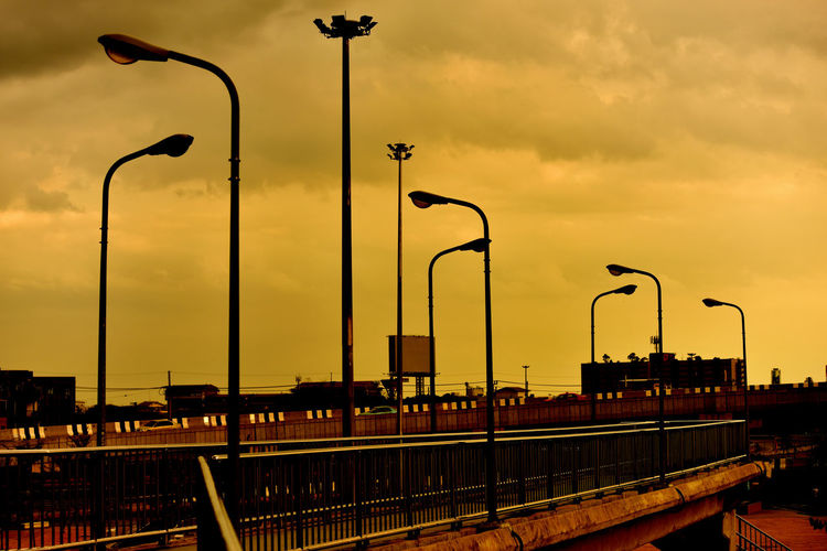 Street lights by bridge against sky during sunset