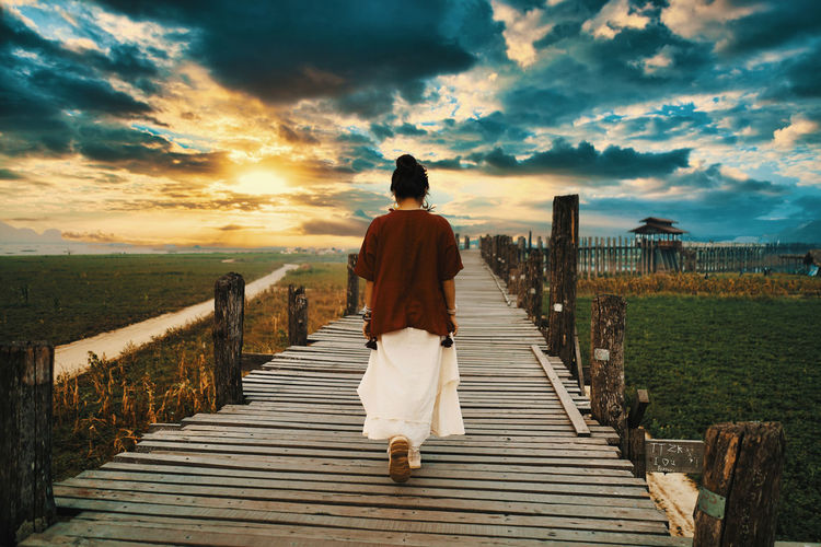 Rear view of woman walking on boardwalk against sky during sunset