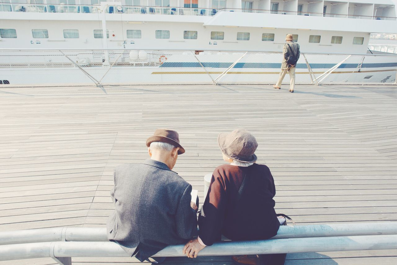 Rear view of man and woman sitting on railing