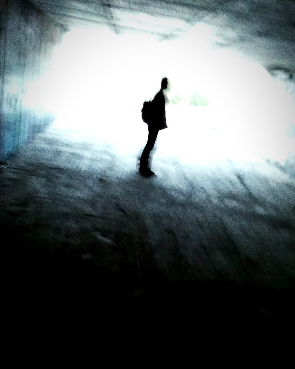 Silhouette Of Man Standing In Tunnel